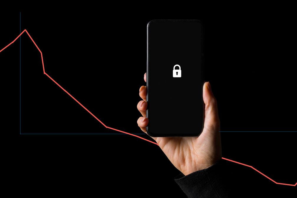 Hand holding an iphone with a lock icon on its screen in front of a graph with a downward trajectory