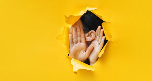 person listening through hole in a yellow wall